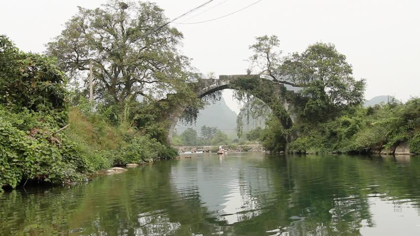 Beautiful Yulong river with ancient stone arch bridge. - Yangshuo Guilin,