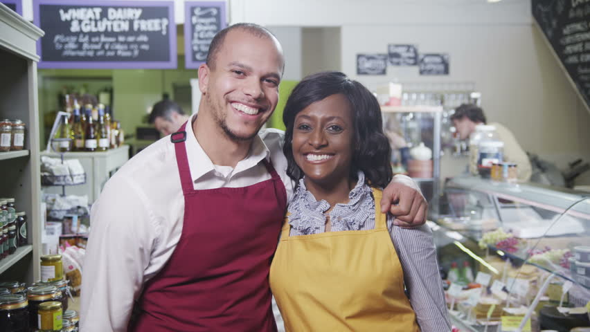 Portrait of happy male and female workers of mixed ethnicity in a delicatessen or whole foods store.