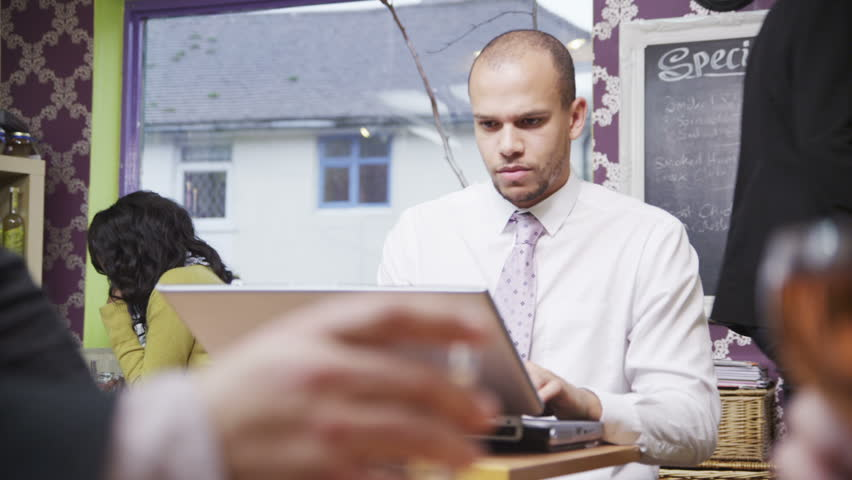 Attractive mixed race young professional male working or social networking, on a laptop computer in a cafe or coffee shop.  | Shutterstock HD Video #4483724