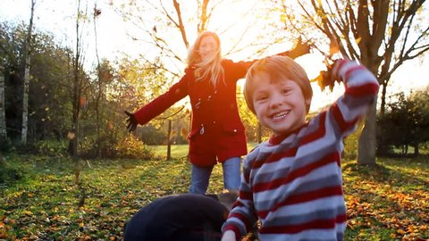 Happy family playing outdoors with autumn leaves. High quality HD video footage
