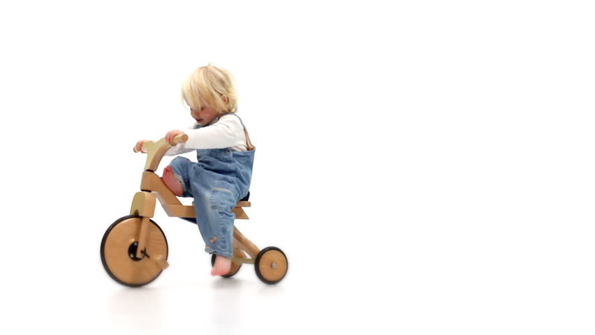 Cute young baby girl playing on a tricycle in white studio