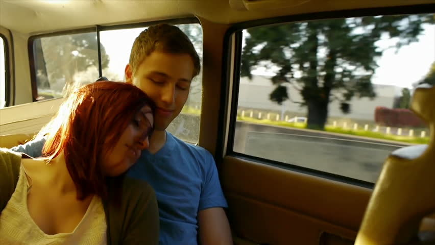 Young Couple Holding Hands In Moving Car