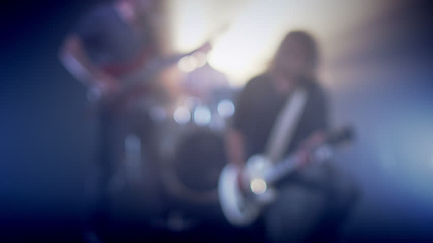 Concert rock band performing on stage with singer performer, guitar, drummer. Music video punk, heavy metal or rock group. Slow motion instrument playing band of men.