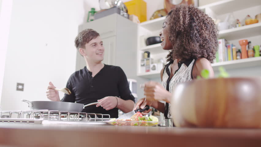 Young people cooking. Student house accommodation. Flat share with teenagers or young adults preparing healthy food.