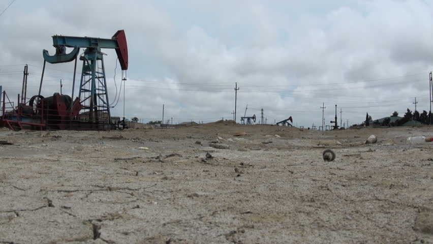Pollution and desertification symbolize the consequences of the use of oil. Desert, arid, garbage, oil donkey (pumpjack)