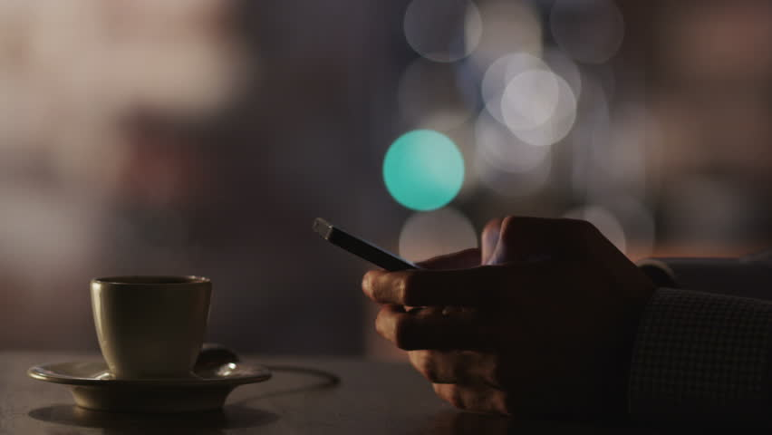 Man Typing a Message Using Mobile Phone at Evening Time in Coffee House. Close-Up. Shot on RED Digital Cinema Camera in 4K, so you can easily crop, rotate and zoom, without losing quality! | Shutterstock HD Video #4520114