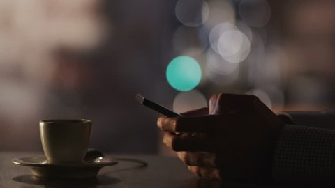 Man Typing a Message Using Mobile Phone at Evening Time in Coffee House. Close-Up. Shot on RED Digital Cinema Camera in 4K, so you can easily crop, rotate and zoom, without losing quality!