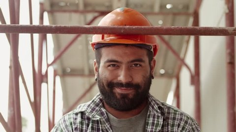 Young latino man at work in construction site, portrait of happy manual worker smiling and looking at camera. Part 1 of 11