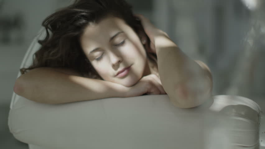 Beautiful brunette model in black lingerie relaxes in her boudoir with sunlight shining on her face.