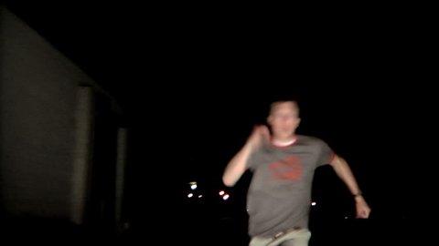 Terrified man running in street at night