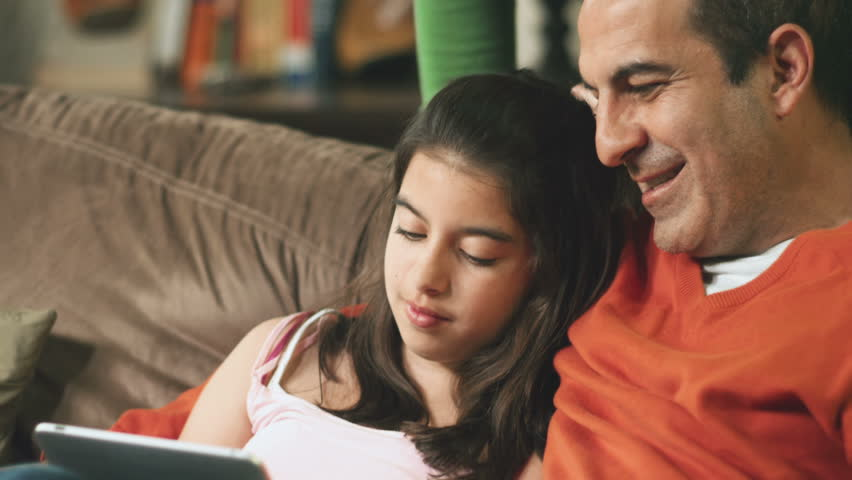 Young girl sits with her dad on the couch in the living room and plays on a digital tablet computer.  Her mom watches them from behind. | Shutterstock HD Video #4552094