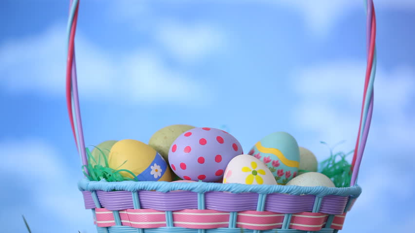 Animation of painted easter eggs in a basket seamless looping hd clouds move by easter basket sitting in grass hd stock video clip negle Gallery