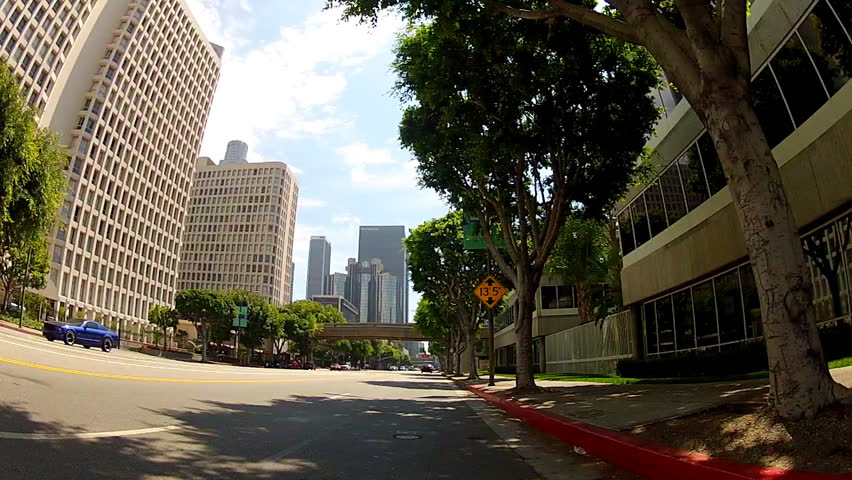 Point of view shot of riding a bicycle in downtown Los Angeles. Features a wide view from the front of a bike as it travels the street underneath shade trees and buildings.  | Shutterstock HD Video #4554614