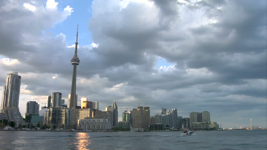 Time-lapse of the Toronto skyline. Tall buildings, CN Tower, water, boats and fast moving clouds.