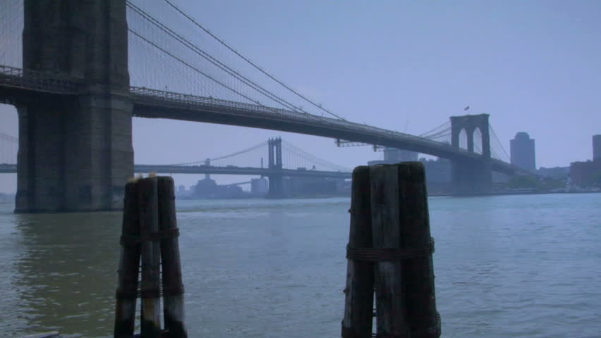 A bridge in New-York city on a foggy day. It could be either dusk or dawn. The water is very quiet.