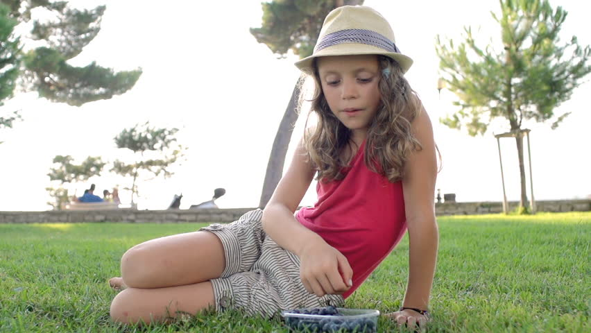 Slow Motion Shot Of A Cute Little Girl Eating Blueberries Out In The Park