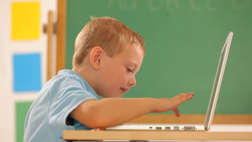 Young boy at school typing on laptop computer