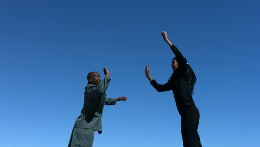 Businesspeople jumping in air doing high five, slow motion