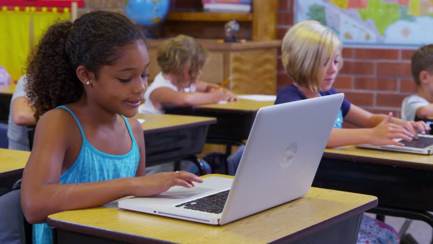 Elementary school students work on laptop computers