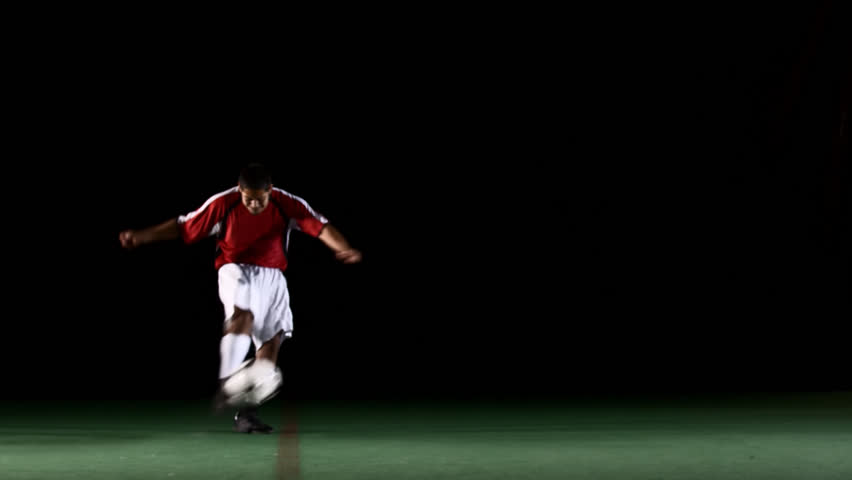 A soccer, or football, player that is dramatically and artistically lit, on an artificial field pitch on a black background, runs up and kicks the ball very hard and fast