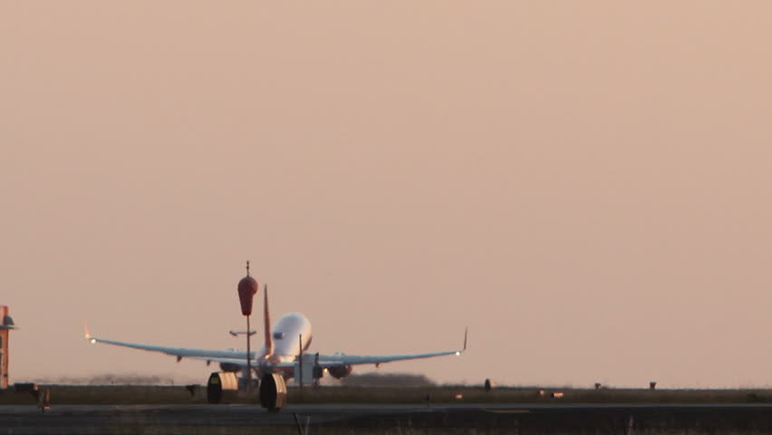 HD footage of a twin engine plane taking off in silhouette against an dusky orange sky.