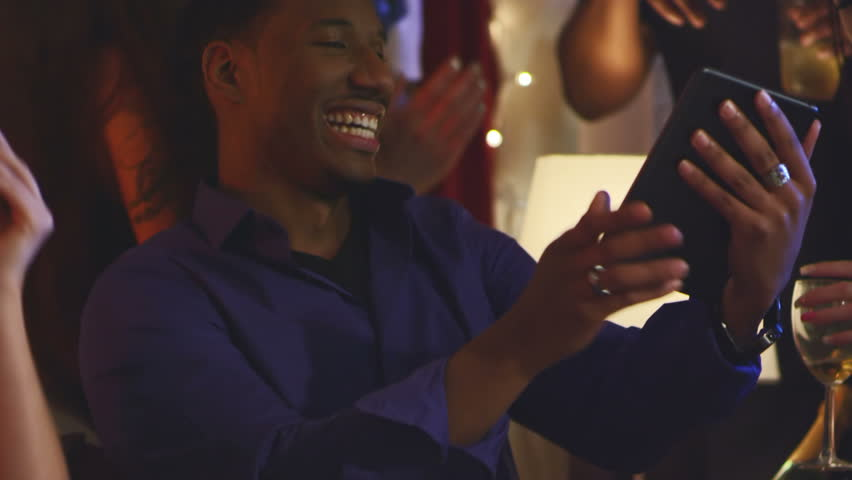 A group of friends sit around a guy with a digital tablet and laugh at what he shows them. Close up shot.