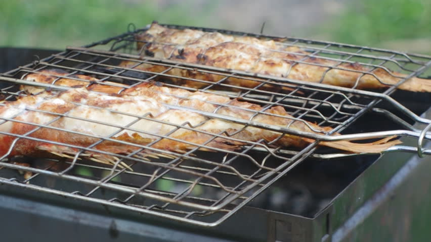 Rock Fish on the grill with flames . grilling sea fishes on campfire grate