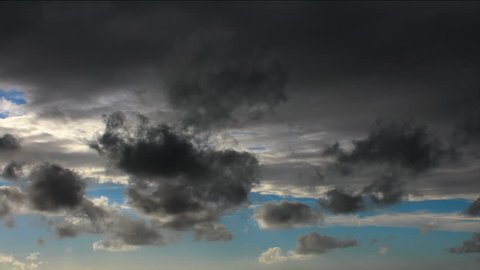 Time lapse sequence of storm clouds clearing to reveal blue sky.