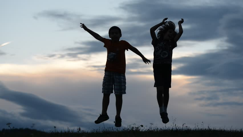Happy children running, jumping and playing on meadow, silhouettes at summer sunset