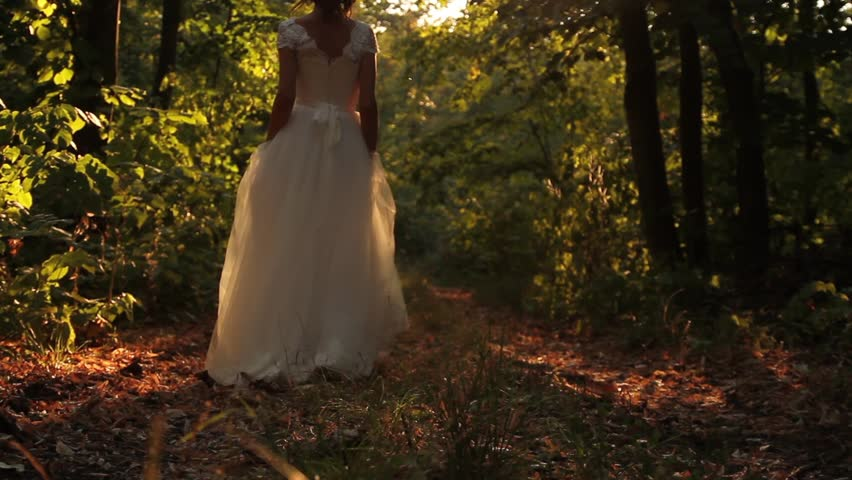 Young Woman in Vintage Wedding Dress walking Forest Background
