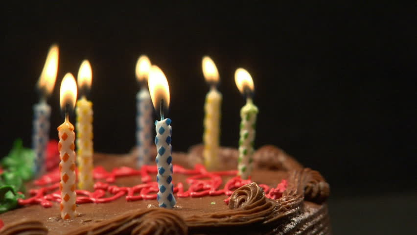 Close up of a birthday cake with candles burning on top