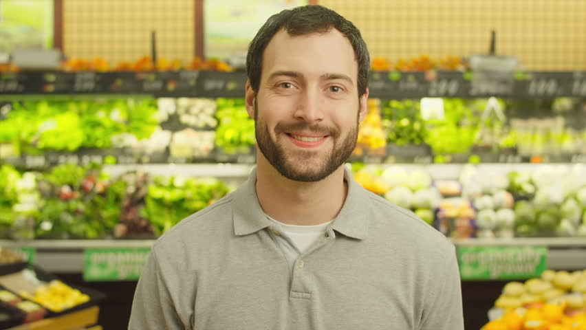 A young man walks up and smiles for the camera while in a produce section of a grocery store. Close up shot. | Shutterstock HD Video #4658351