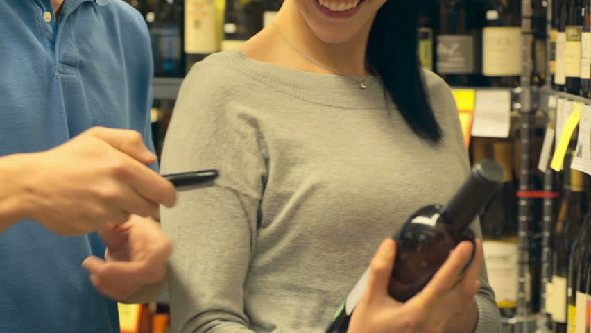 A man uses a cell phone to look up different wines as he and his significant other look through the wine selection at a grocery store. Close up shot.