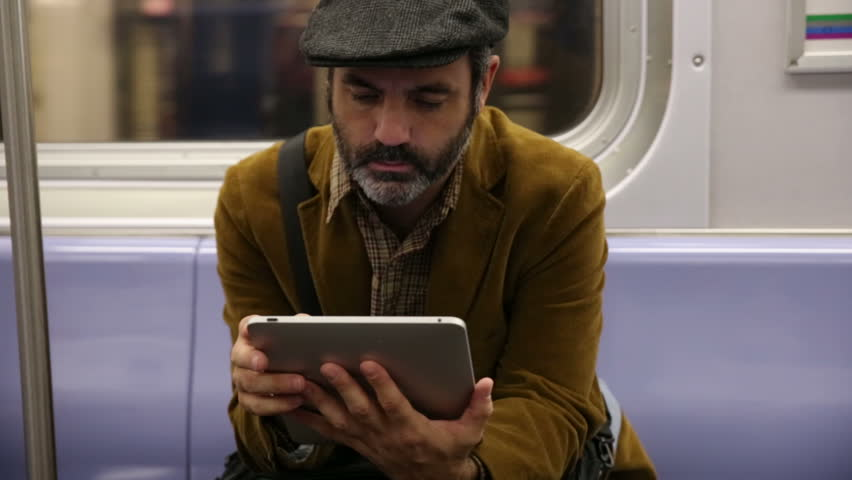 Man uses digital tablet on subway