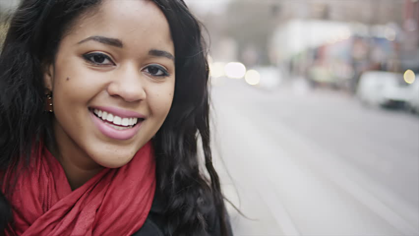 A young woman is waiting for her bus as she turns and smiles for the camera. Close up shot.