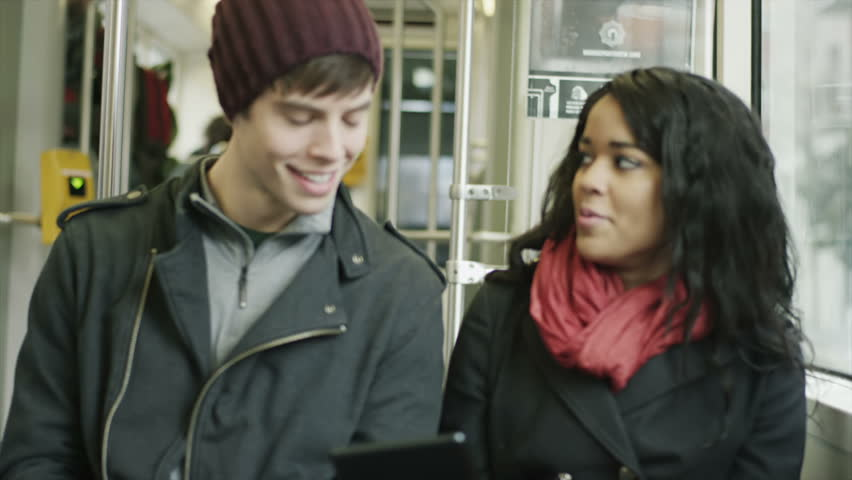 A cute couple sits together on a tram having fun looking for through their tablet computer.