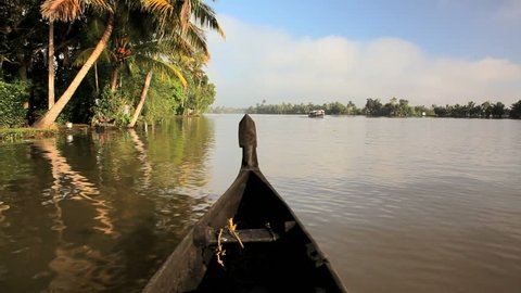 POV river canoe of water traffic on the Kerala river backwaters, Alleppey, Kerala, India