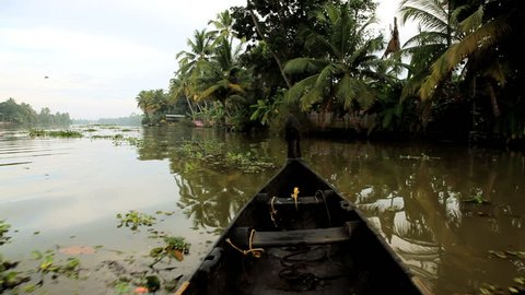 View of a quiet strech of rural river with a local man bathing in the shallows in the Kerala backwaters near Alleppey, India