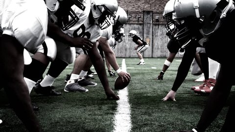 The defensive and offensive lines of two football teams meet at the line of scrimmage. High contrast, with camera flashes and time remap.