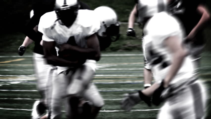 A Running Back receives a handoff and spins to avoid a defender. High contrast, with flashes and time remap. | Shutterstock Video #4681913