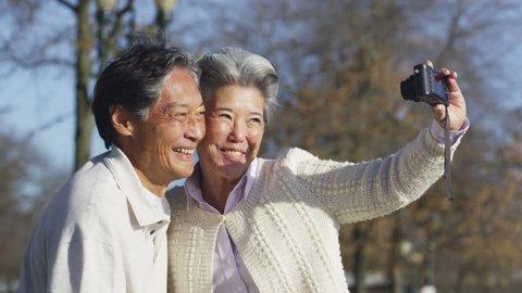 Senior couple with camera taking photo together