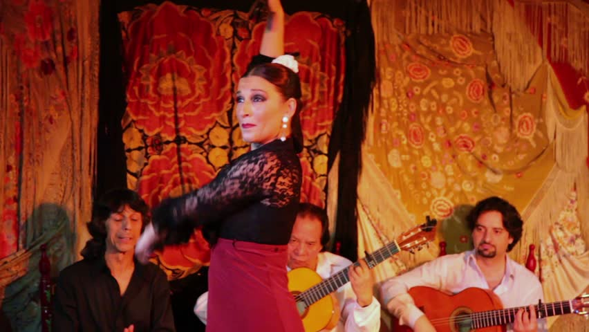 MADRID - MARCH 9: Woman dances in flamenco style with castanets and musicians support at small stage in cafe on 9 March 2012 in Madrid, Spain. Youth unemployment in Spain has exceeded 43% in 2011