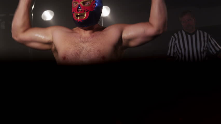 Masked wrestler in boxing ring flexing muscles