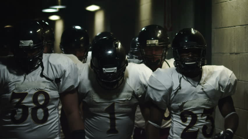 Football team walks down a dark tunnel towards the field before a game #4706294