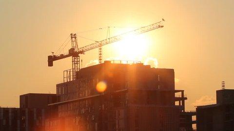 Sunset crane. Tower crane and condominium at sunset. Time lapse shot.