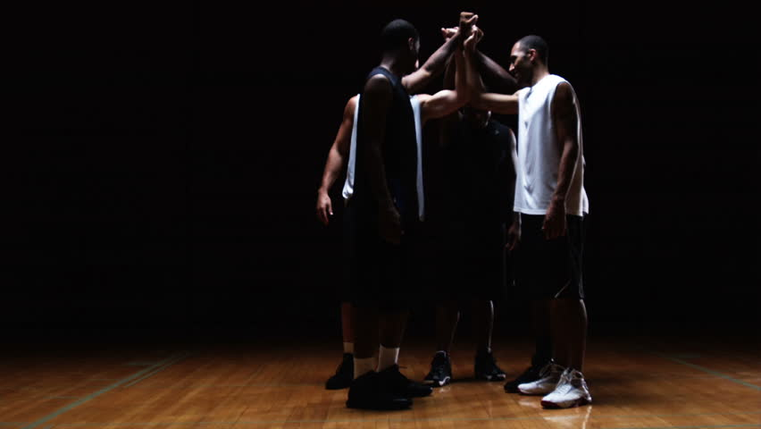 Wide shot of a group of basketball players in a huddle putting their hands in the middle and breaking | Shutterstock HD Video #4712294