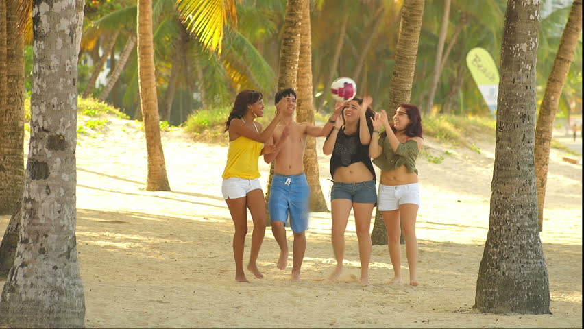 A group of four teenagers walk through the trees while on the beach