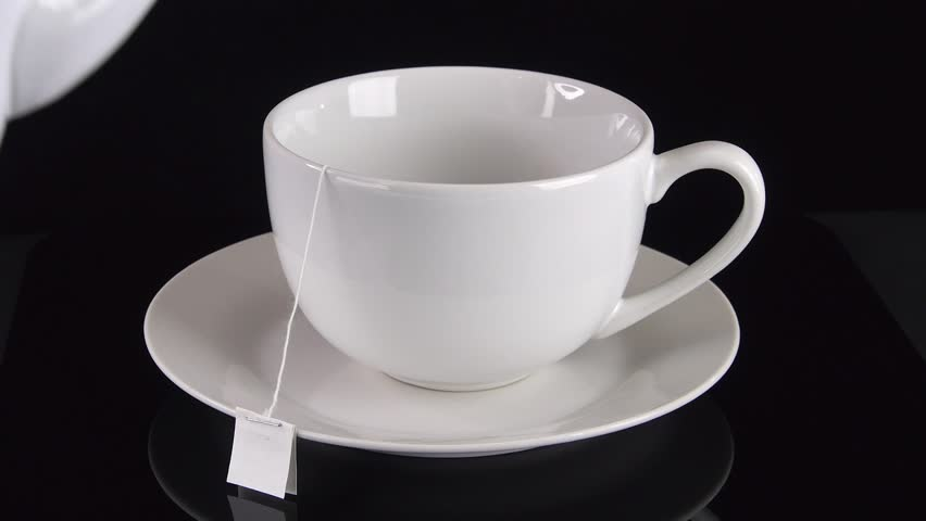 Angled top view of hot water being poured from a teapot into a white cafe-style tea cup on a saucer against a black background with steam.