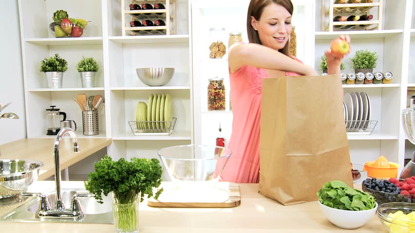 Caucasian woman returning home from grocery shopping with a large bag full of assorted organic fruit