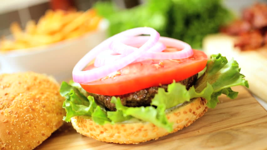 Close up of organic salad ingredients placed on delicious grilled ground beef burger on a sesame seed bun